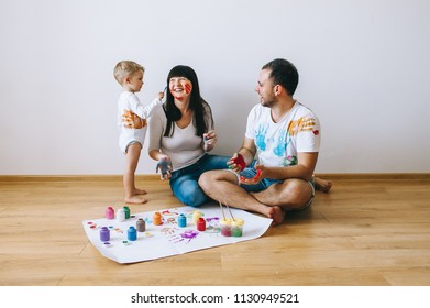 Joy family art happy father  mother and son show hands in bright colors paint together picture art