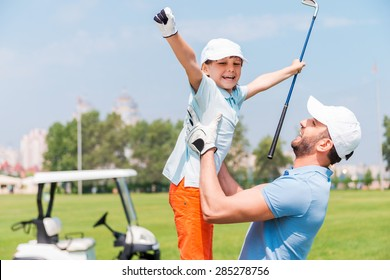 Joy of great game. Excited young man picking up his son while standing on the golf course