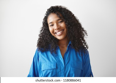 Joy, happiness, success, positiveness and good mood concept. Picture of fashionable beautiful young mixed race female with brown perfect skin, wavy black hairdo and broad smile posing in studio