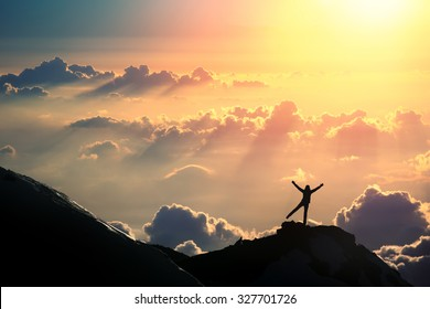 The joy of life. A person is standing on the top of the mountain above the clouds.