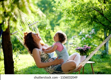 Joy. Mother and baby girl in hammock laughing in summer garden. Family, happiness, smiling, nature, people