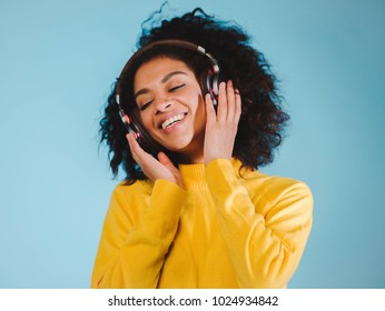 Joy and music. Colorful studio portrait of happy afro young brunette woman with earphones is dancing and singing.