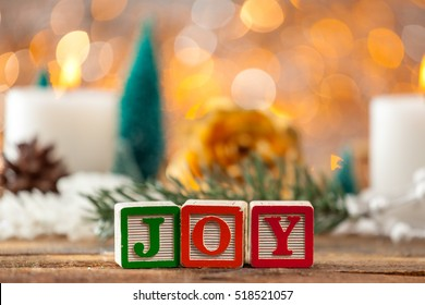 Joy Written With Toy Blocks On Christmas Card Background With Copy Space.
