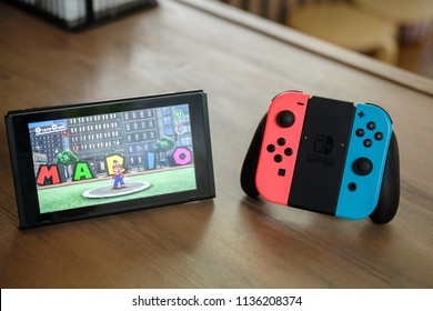 Joy-con controllers and console Nintendo Switch on table indoor, gamepad and video game console for home or portable gaming. Screen showing game Mario Odyssey