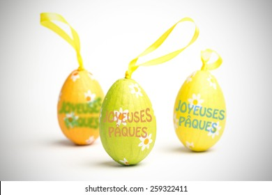 joyeuses paques against three foil wrapped easter eggs
