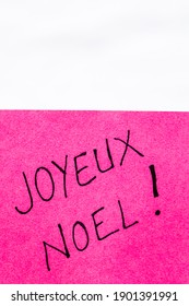 Joyeux noel (Merry Christmas) handwriting text close up isolated on pink paper with copy space. Writing text on memo post reminder