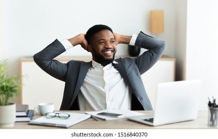 Joyful african american businessman relaxing at workplace, leaning back in chair in modern office, panorama