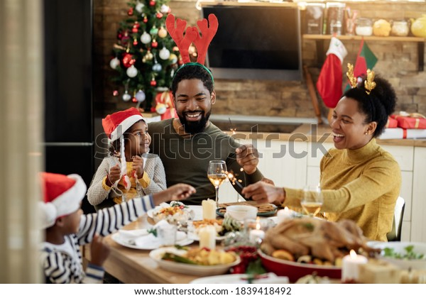 Joyful African American family using sparklers while having lunch and celebrating Christmas at dining table.