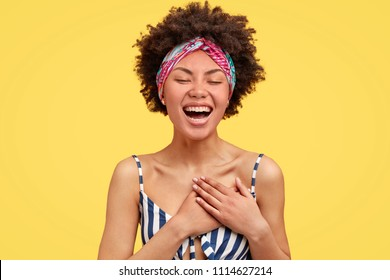 Joyful African American female youngster expresses happines, laughs pleasantly, keeps hands on heart, wears casual clothes, closes eyes in pleasure, stands against yellow background. Emotions concept