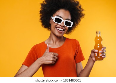 Joyful african american girl in sunglasses drinking soda and showing ok sign isolated over yellow background