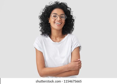 Joyful African American student keeps hands crossed, laughs at good joke, wears casual clothes and round spectacles, isolated over white background. Happy young woman with dark skin poses indoor