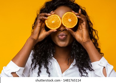 Joyful african american woman holding orange slices next to eyes, imitating kissing, yellow studio background