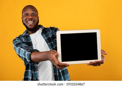 Joyful African Man Showing Empty Digital Tablet Screen To Camera Recommending New Application Standing Over Yellow Studio Background. Advertisement Banner With Tablet Computer Display Mockup - Shutterstock ID 1931024867