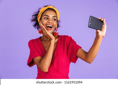 Joyful african woman in dress making selfie on smartphone while touching her cheek over purple background