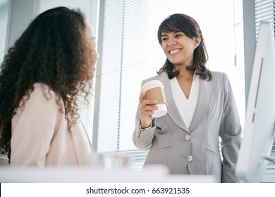 Joyful Asian businesswoman with paper cup of coffee in hand talking with her colleague while taking short break from work, panoramic window on background