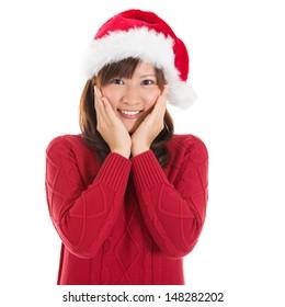 Joyful Asian Christmas woman wearing santa hat. Christmas woman portrait of a cute, beautiful smiling Asian Chinese / Japanese model. Isolated on white background.
