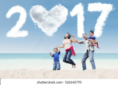 Joyful Asian family jumping together on the beach with cloud shaped numbers 2017, shot outdoors