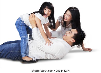 Joyful asian family laughing and playing together on the floor, shot in the studio isolated on white