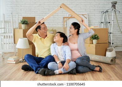 Joyful Asian family making roof from cardboard box over their heads and looking at each other with wide smiles while sitting on floor of new apartment surrounded with moving boxes