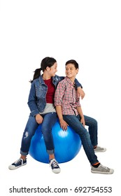 Joyful Asian kids sitting on fitness ball and looking at each other