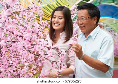 Joyful Asian senior man standing with his young daughter close to cherry tree and enjoying its smell, waist-up portrait