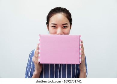 Joyful asian thai woman with pink gift box isolated on white background. Beauty and fashion.