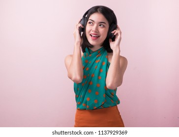 joyful asian woman wearing headphone and listening music from app in smartphone.