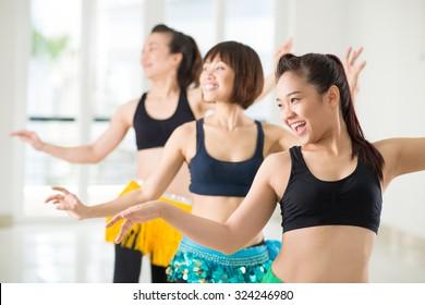Joyful Asian women performing belly dance in studio