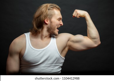 joyful athlete admiring with his strong arms isolated on the black background. happy result after workshop. look at the biceps