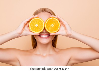 Joyful attractive charming cheerful toothy funny comic positive nude natural girl with beaming smile making binoculars with two pieces of orange, closing eyes, isolated on beige background