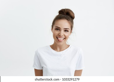Joyful attractive european woman with stylish hairstyle showing tongue and smiling, being in good mood while standing against white background. Childish girlfriend won bet and now rejoicing