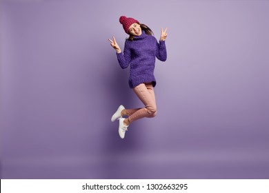Joyful attractive girl jumps over purple background, makes peace sign, tilts head, dressed in winter clothes, expresses happiness, poses for making cool photo, isolated. Good emotions and feelings