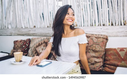 Joyful attractive young Asian woman in off-shoulder blouse sitting at table with cup of coffee and smartphone in tropical cafe