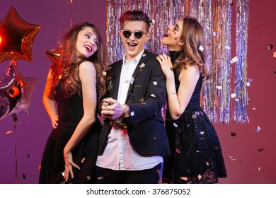 Joyful attractive young man dancing and having fun with two seductive happy young women over purple background