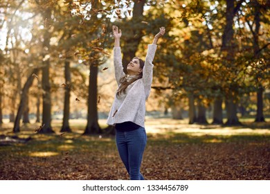 Joyful attractive young woman throwing autumn leaves into the air above her head with a happy smile outdoors in a park with colorful fall foliage on the trees
