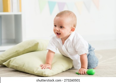 Joyful baby crawling on the floor in nursery room