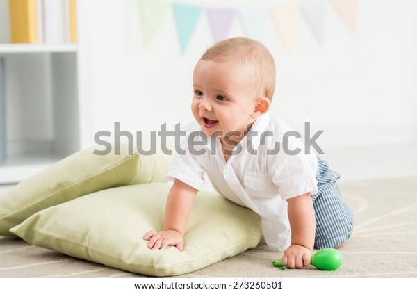 Joyful baby crawling on the floor in nursery room