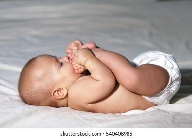 Joyful baby is tasting its own legs