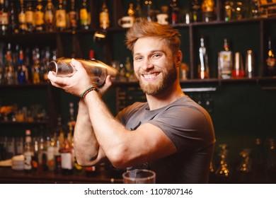 Joyful bartender mixes a cocktail in a shaker