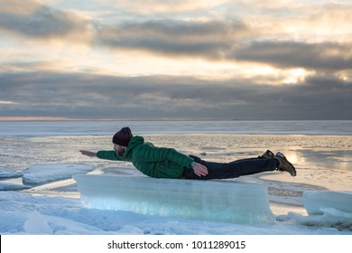 Joyful bearded man in green jacket, jeans lies and surfing on ice floe in winter day/ man lies on an ice floe against the frozen sea, cloudy sky on backround/