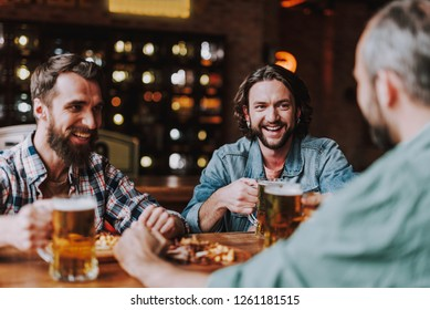 Joyful bearded men sitting at the table while holding mugs of beer and laughing