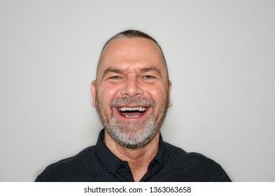 Joyful bearded middle-aged man laughing at the camera enjoying a good joke over a grey studio background