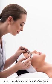 Joyful beautician lengthening female eyelashes