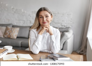 Joyful beautiful 60 year old female literature teacher looking at camera with charming smile while sitting at her workplace, having coffee break; mug, copybook and book resting on wooden desk