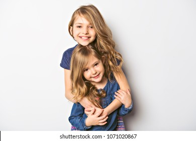 Joyful beautiful child with her sister close to a white wall