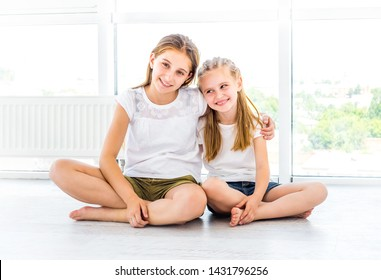 Joyful beautiful child with her smiling teenister close to large windows in white room
