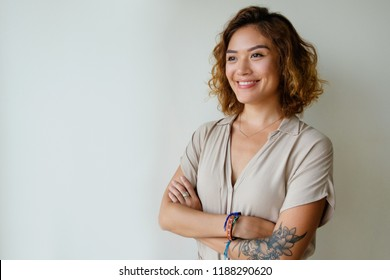Joyful beautiful Chinese girl looking away. Smiling young Asian woman posing with arms crossed. Female portrait concept