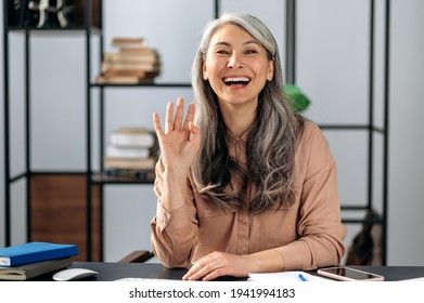 Joyful beautiful confident gray-haired Asian woman, freelancer, business lady, manager, chatting on a video call, conducts online briefing with colleagues or friends, gesturing with her hand, smiling
