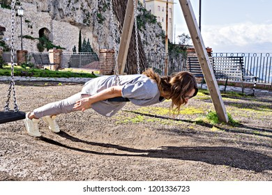 Joyful, beautiful hipster girl in casual look and windy hair, fooling around on swing planking, deadpan style photo, instagram effect