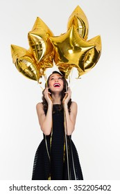 Joyful beautiful young female with bright makeup in retro style holding and looking up on star shaped balloons
